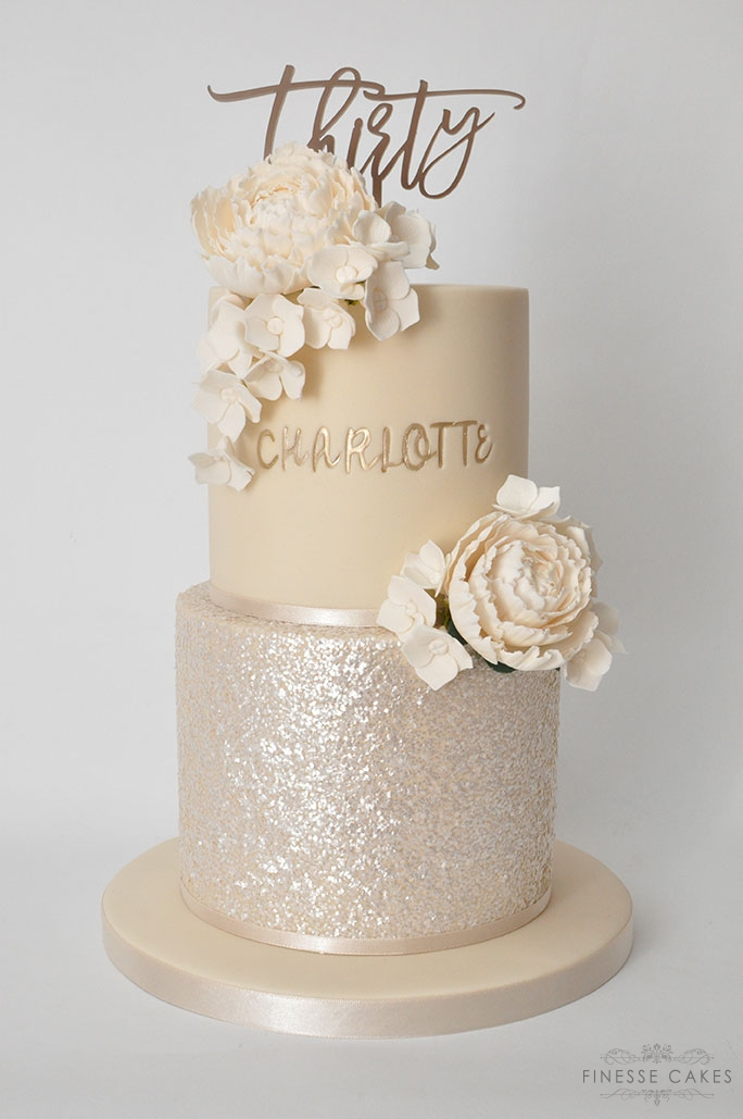champagne gold sparkle 30th birthday cake for a lady with peony and hydrangea flowers finesse cakes essex